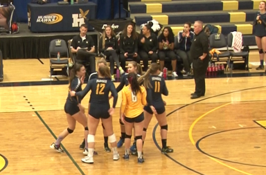 Photo of group of women in black and yellow volleyball uniform celebrating on a court.