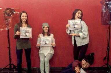 4 Students posing against a red wall holding white festival winner certificates