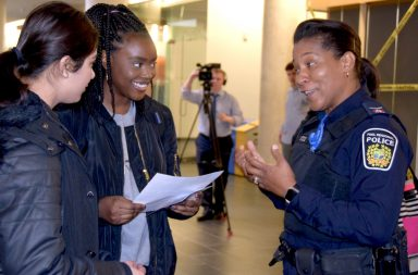 Two students holding a piece of white paper speak to a female police officer
