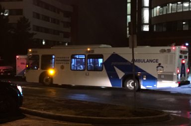 Image of bus at night parked in front of building.