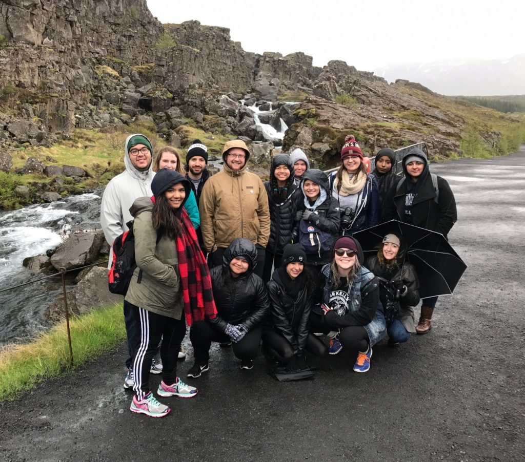 Group of students dressed in rain gear pose in front of a green cliffy landscape