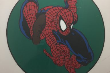 Photo of spiderman in a green circle on a sign with the store name Excalibur Comics surrounding