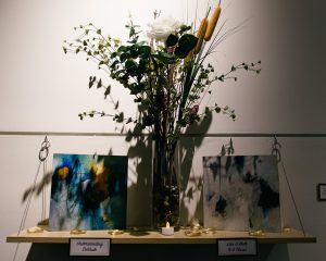 Two painted canvases on either side of a vase of flowers sitting atop a shelf.