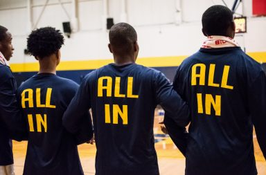 Three basketball players stand with their backs towards the camera with their arms linked together.