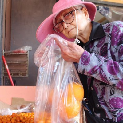 woman wearing hat at grocery store, picking out oranges and putting them into a plastic bag