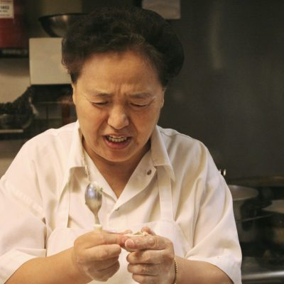 woman in hair net holding spoon and making dumplings