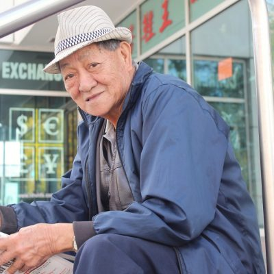 old man wearing a hat sits on the steps of Chinatown reading a newspaper
