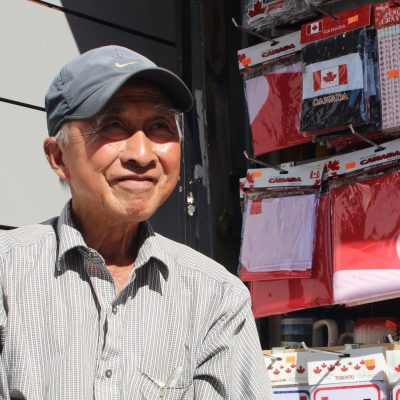 old man wearing hat selling canadian sovenirs