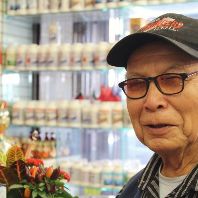 old man wearing hat at herbal store