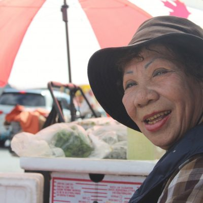 woman wearing hat sells produce on the chinatown street