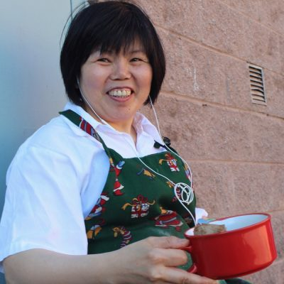 woman smiling and wearing an apron and holding onto her lunch container during her break