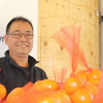 man smiling with oranges in red bags