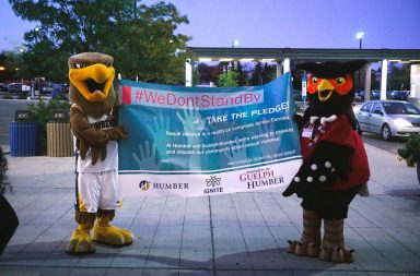 Humber College Mascot Hawk and Univeristy of Guelph-Humber mascot Swoop the owl hold a sign in support of sexual assault survivors