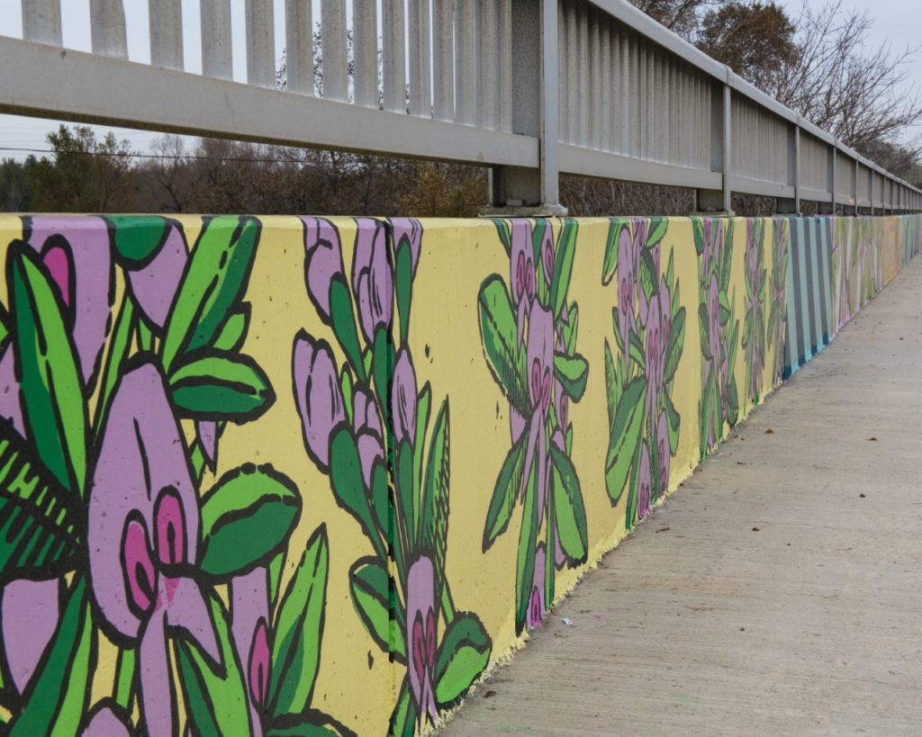 Concrete bridge with a yellow painted background with flowers