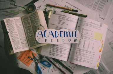 """Photo of messy papers scattered throughout the frame. Writing utensils, tape and scissors are surrounding two open books. The words """"Academic Freedom"""" are written on a piece of paper in blue marker with pencil traces around it."""