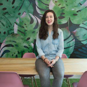 Rachel Kelly sitting on top of a desk.