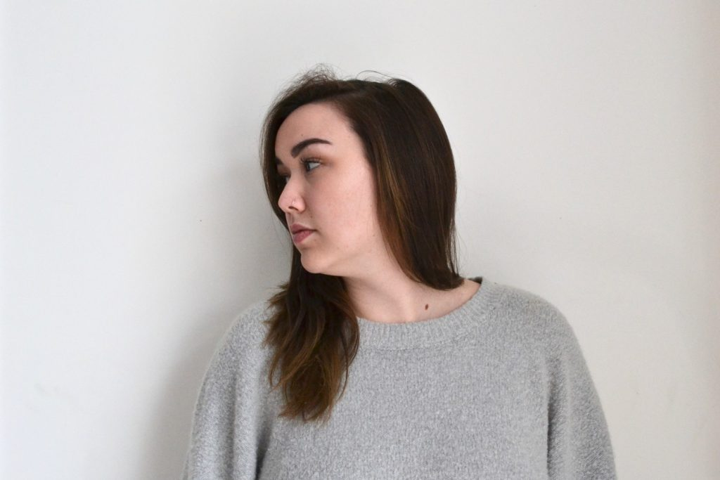 Portrait of female student in grey sweatshirt against wall with head turned left and looking away.