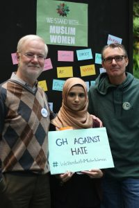 "Hira Zulfiqar stands with two professors holding a board that reads ""GH Against Hate."""