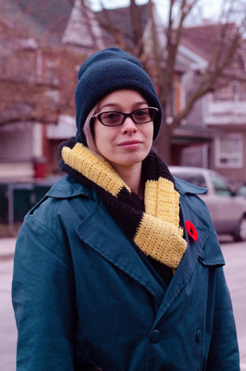 Image of person wearing navy hat, navy and yellow scarf and a navy jacket with a poppy on.