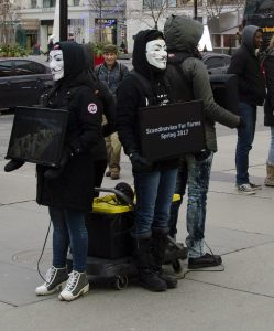 Group of people holding screens with masks on