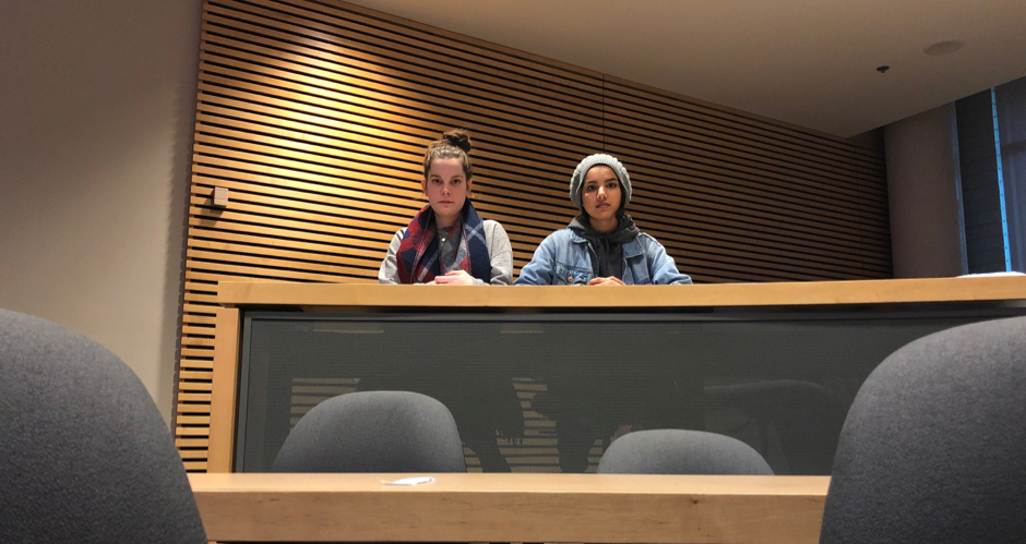 Two students sit at a table in a lecture theatre