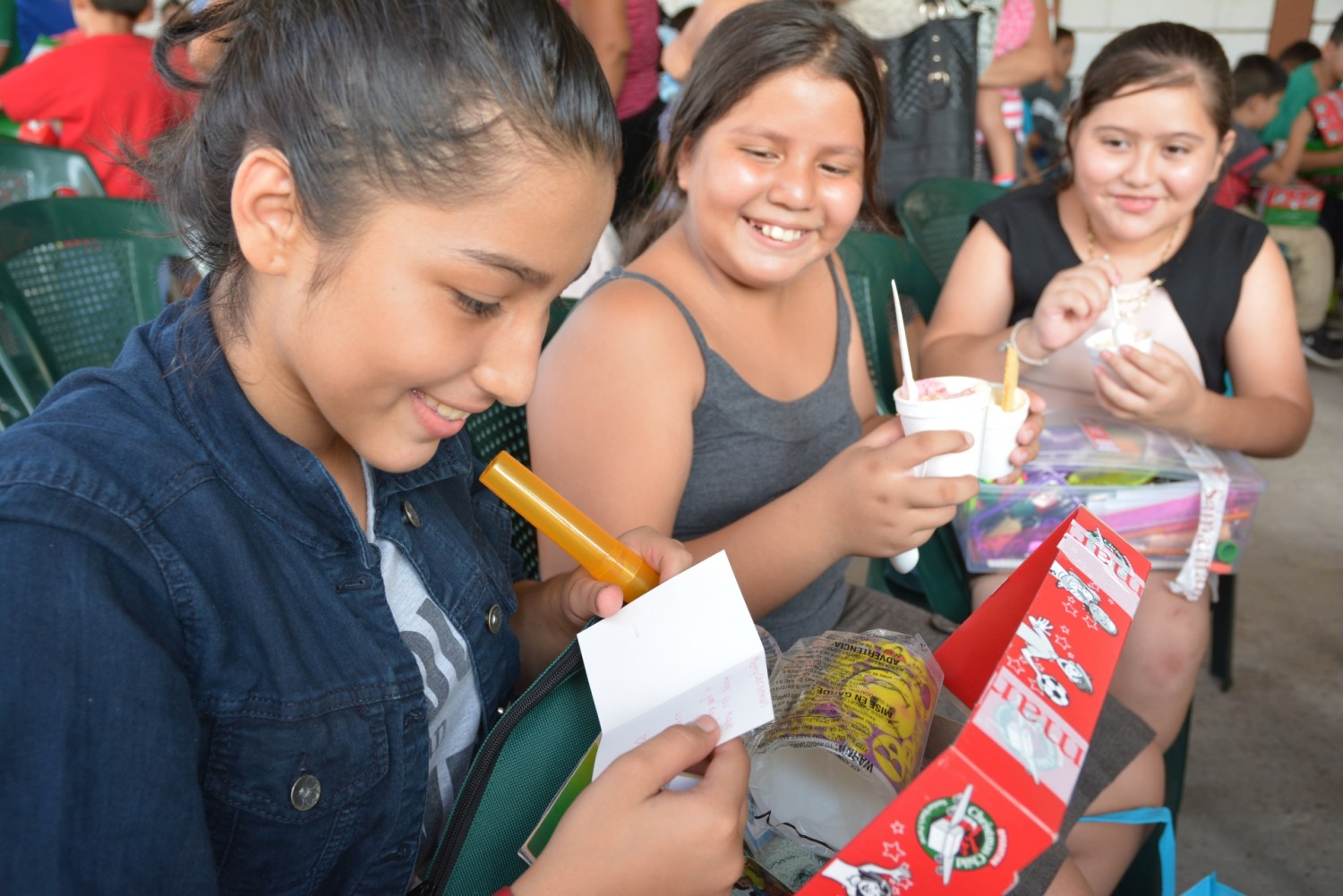 Three young girls open their shoeboxes in El Salvador.