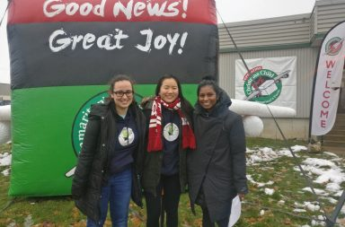 Students Alicia Colabito and Carey Wong as well as Aren Sammy stand outside the Operation Christmas Child warehouse.