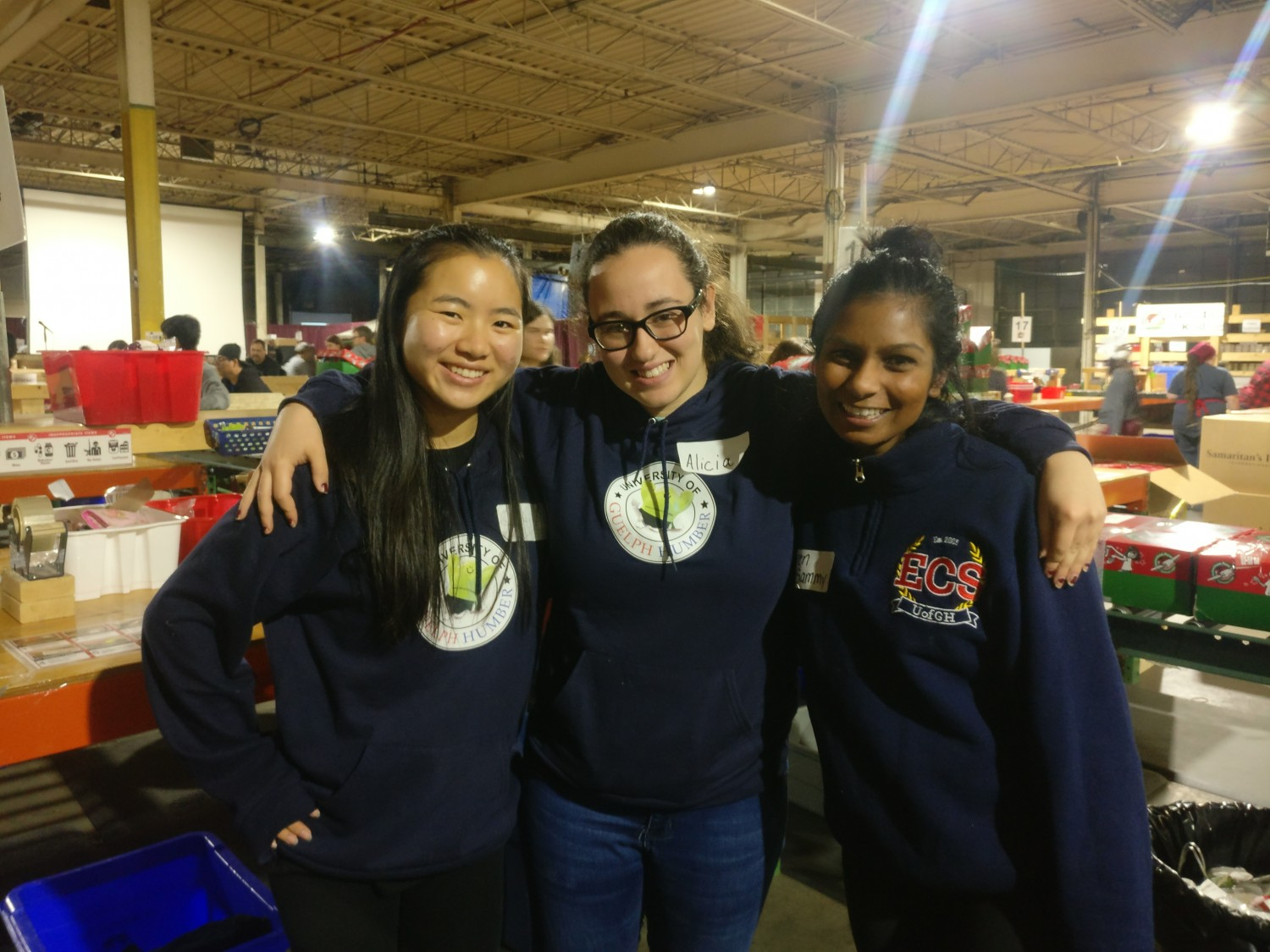 Students Carey Wong and Alicia Colabito along side Aren Sammy at the inspecting table in the warehouse of Operation Christmas Child.