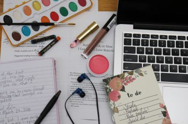 Picture of school notes, laptop, art supplies and make up products.