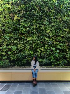 girl sitting in front of plant wall
