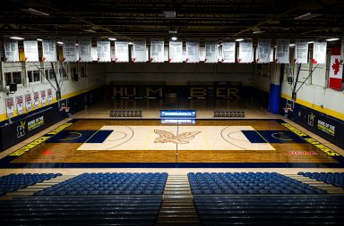 Panoramic view of Humber North Campus gym with spotlights high lighting the basket ball court and the banners hanging in the rafters.