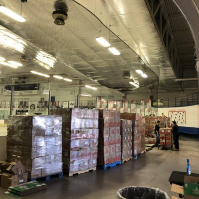Food bank items await distribution in a hockey arena