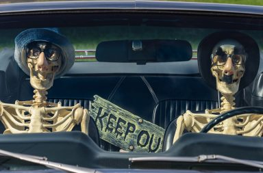 Two skeletons sitting in a car with funny masks and a keep out sigh behind them