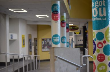 A photograph of an empty hallway at Humber college. Pillars with colourful dots and positive affirmations line the right side of the hallway.