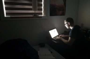 Man hunched over computer taking notes