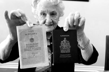 Black and white photo of an elderly lady holding up a Canadian and Austrian passport