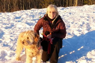 Katherine Polack dressed in winter gear with her large white dog Bella, kneeling in the snow.