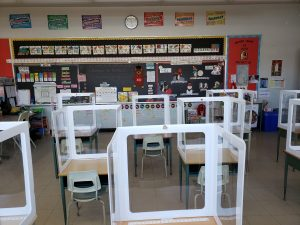 Multiple desks in a classroom each with their own plexiglass shields facing the chalk board and spread apart.