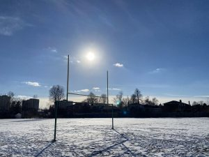 Football uprights in a snowy field on a sunny day