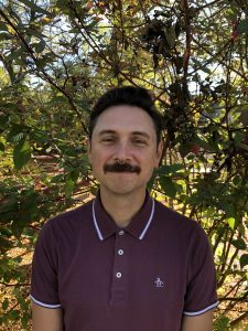 A man with an moustache and nose ring in a maroon shirt at a park