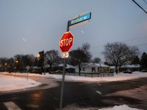 A stop sign with a street sign that says Windsor Road on a snowy evening