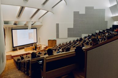 Students with laptops sitting in a university lecture hall